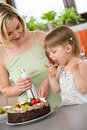 Mother and child with chocolate cake in kitchen Stock Photos
