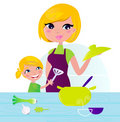 Mother with child cooking healthy food in kitchen Royalty Free Stock Photos