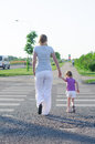Mother and child crossing the road back view Stock Image