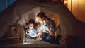 Mother and child daughter with a book and a flashlight before go Royalty Free Stock Photo