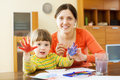 Mother and child drawing with hand printing happy her on paper Royalty Free Stock Photography