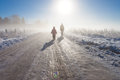 Mother and child on foggy snow farm road near fence Stock Photo