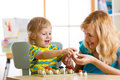 Mother and child learn color, size, count while playing with developmental toys. Early education concept.