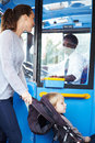 Mother with child in pushchair boarding bus looking at driver Stock Photography