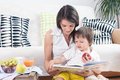 Mother and child, reading a book and eating fruits Royalty Free Stock Photo