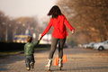 Mother and child roller skating with her in the park Royalty Free Stock Photography