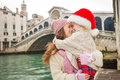Mother and child in Santa Hat hugging near Ponte di Rialto Royalty Free Stock Photo