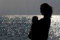 Mother and child silhouette on the blue sea Stock Photography