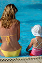 Mother and child sit in swimming pool Stock Photos