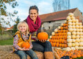 Mother and child sitting on haystack portrait of happy holding pumpkins Royalty Free Stock Image