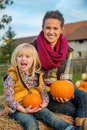 Mother and child sitting on haystack portrait of happy holding pumpkins Stock Photos