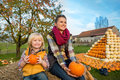 Mother and child sitting on haystack with pumpkins happy Royalty Free Stock Photos