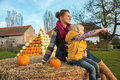 Mother and child sitting on haystack with pumpkins pointing Royalty Free Stock Photos