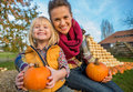 Mother and child sitting on haystack with pumpkins portrait of smiling Stock Image