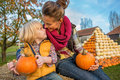 Mother and child sitting on haystack with pumpkins smiling Stock Photos