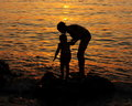 Mother and child sunset wallpaper stock picture silhouettes against sun light on evening sea background Royalty Free Stock Photos