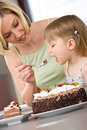 Mother and child tasting chocolate cake in kitchen Stock Photo