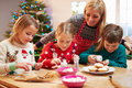 Mother and children decorating christmas cookies together in kitchen at home Royalty Free Stock Photo