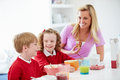 Mother and children having breakfast in kitchen together looking at each other smiling Royalty Free Stock Photos