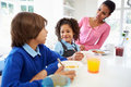 Mother and children having breakfast before school sitting at table in kitchen eating cereal Stock Images