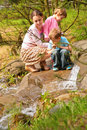 Mother with children look on little waterfall Stock Photo