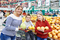 Mother and children with pineapples in fruit department in super Royalty Free Stock Photo