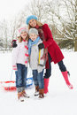 Mother and Children Pulling Sledge Through Snow Stock Photos