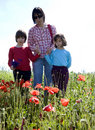 Mother and children in red poppy Royalty Free Stock Photo