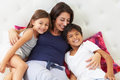 Mother and children relaxing in bed wearing pajamas smiling to camera Royalty Free Stock Photos