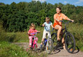 Mother with children ride bikes outside city Royalty Free Stock Images