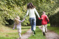 Mother and children running along woodland path Royalty Free Stock Images