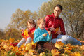 Mother with children sit on fallen maple leaves Stock Photos