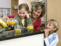 Mother and children standing beside breakfast bar in kitchen woman pouring orange juice women Stock Image
