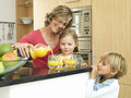 Mother and children standing beside breakfast bar in kitchen woman pouring orange juice women Royalty Free Stock Photography