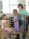 Mother and children standing in kitchen son wearing striped apron smiling side view Stock Photography