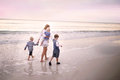 Mother and Children Walking Along Ocean Beach at Sunset Royalty Free Stock Photo