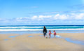 Mother and children are walking on sandy Atlantic beach. Royalty Free Stock Photo