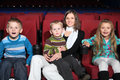 Mother with children watching a movie in cinema admiration Royalty Free Stock Photo