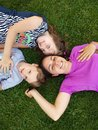 Mother and children young women with her boy son daughter girl lying on the grass smiling Royalty Free Stock Photo