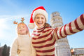 Mother in Christmas hat taking selfie with daughter in Pisa Royalty Free Stock Photo