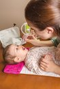 Mother cleaning mucus of baby with nasal aspirator catarrh adorable a Stock Images