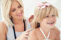 Mother combing daughter s hair mid adult her cute Royalty Free Stock Image