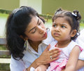 Mother comforting upset indian girl family outdoor modern is her crying daughter Stock Photo
