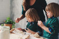Mother cooking with kids in kitchen. Toddler siblings baking together and playing with pastry at home Royalty Free Stock Photo