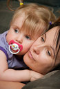 Mother cuddling baby girl Stock Image