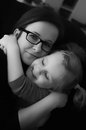 Mother cuddling daughter Stock Photo