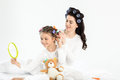 Mother in curlers curling hair to happy little daughter looking at hand mirror Royalty Free Stock Photo