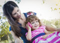 Mother and cute baby daughter playing with cell phone mixed race in park Royalty Free Stock Photography