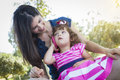 Mother and cute baby daughter playing with cell phone mixed race in park Royalty Free Stock Images