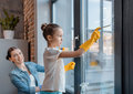 Mother and cute little daughter in protective gloves cleaning window together